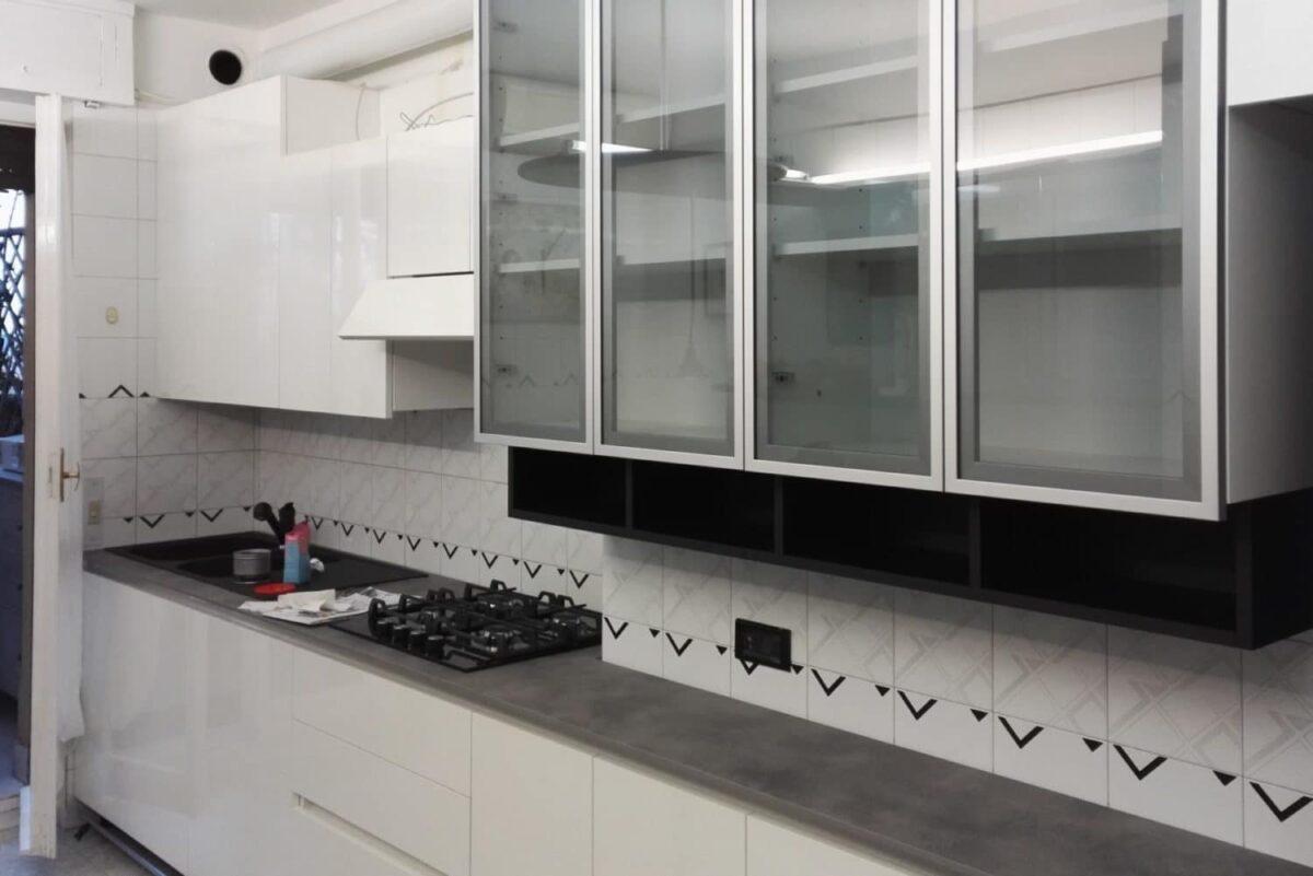 Cucina in nobilitato idro, ante in laminato bianco lucido e vetro alluminio