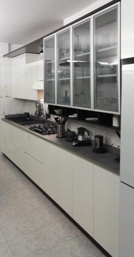 Cucina in nobilitato idro, top in stratificato cemento, ante in laminato bianco lucido e vetro alluminio
