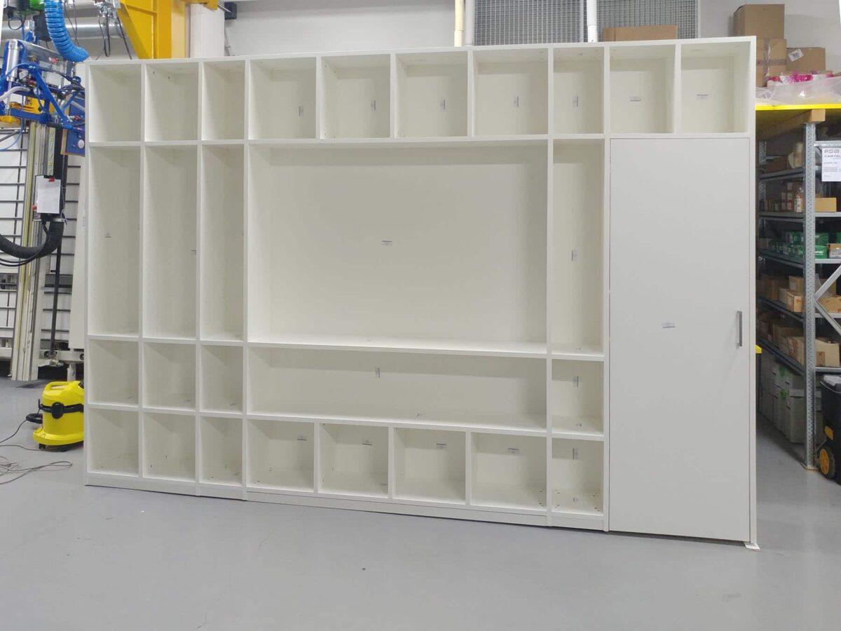 Parete attrezzata con una capiente libreria, un vano schermo TV e porta, pre-montaggio in laboratorio
