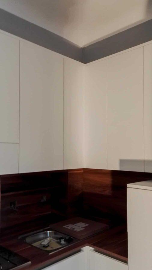 Cucina dalle dimensioni modeste, con schienale e piano di lavoro con la stessa finitura