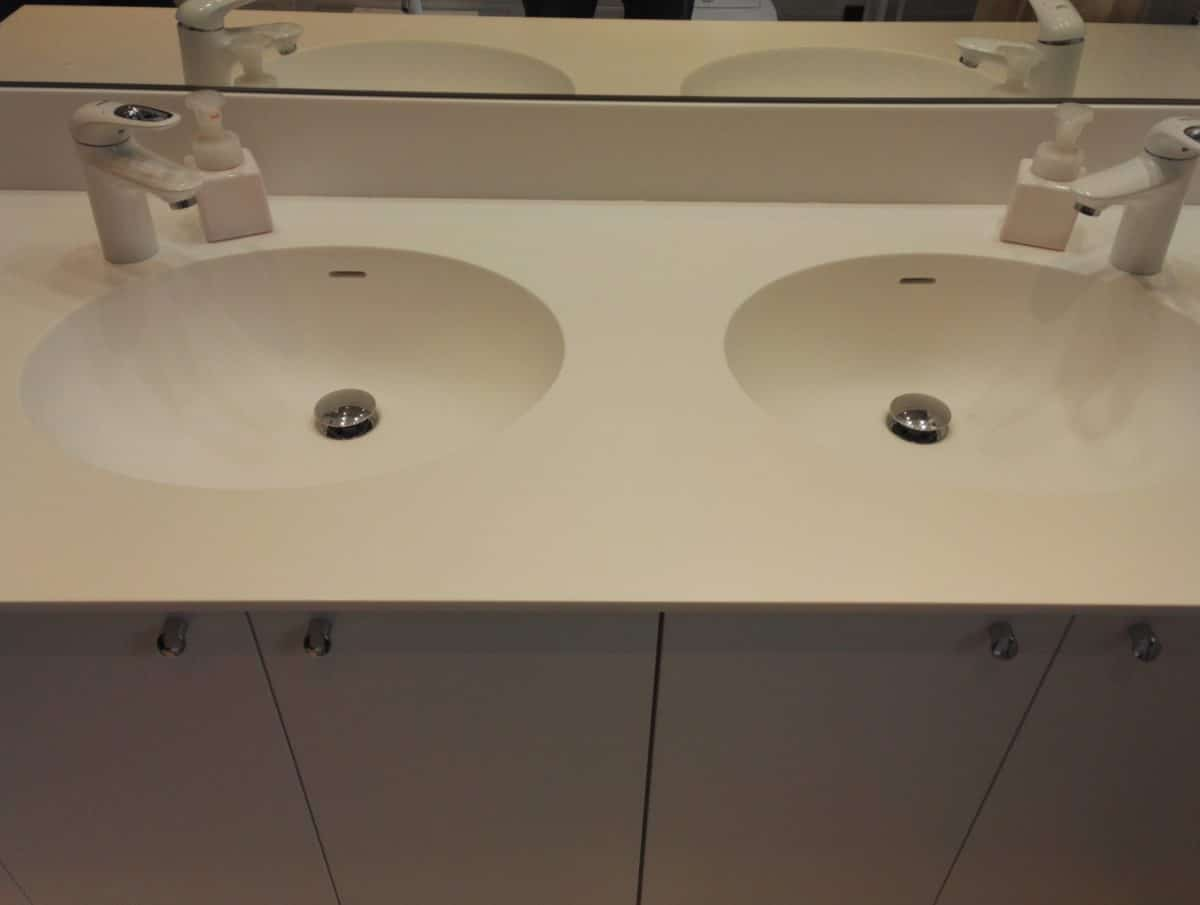 """Arredo bagno con piano in """"solid surface"""" con due lavabi integrati, particolare angolo mensole"""